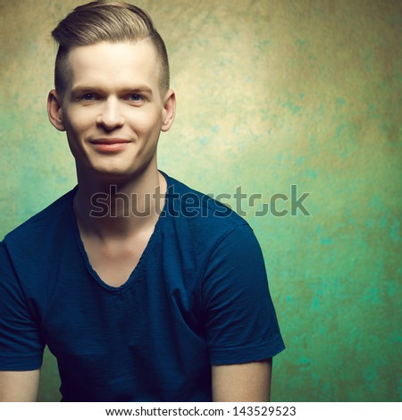 Portrait of a young man with very handsome face in blue casual t-shirt and stylish haircut posing over golden-turquoise  background and smiling. Perfect skin and hair. Copy-space. Studio shot