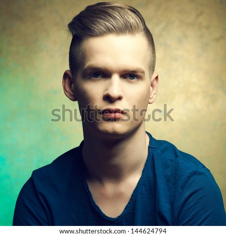 Portrait of a young man with very handsome face in blue casual t-shirt and stylish haircut posing over golden-turquoise  background. Perfect skin and hair. Hipster style. Close up. Studio shot