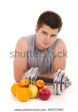 portrait of a young man with weights and fresh fruits