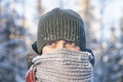 Portrait of a young man wrapped in a scarf. Cold