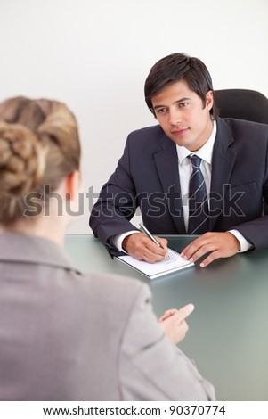 Portrait of a young manager interviewing a female applicant in his office