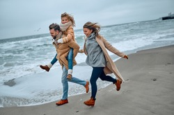 Portrait of a young married couple and their cute daughter who have fun on the beach in winter.