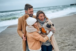 Portrait of a young married couple and their cute daughter who having fun with a dog on the beach in winter wearing warm clothes and scarves in the cold season.