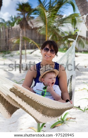 Portrait of a young mother and a cute toddler boy on a tropical beach