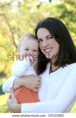 Portrait of a young mother and her blue-eyed baby boy, outdoors in a park, suitable for a variety of seasonal and family themes