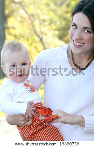 Portrait of a young mother and her blue-eyed baby boy with bright orange and red butterfly, outdoors in a park, suitable for a variety of seasonal and family themes