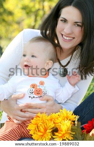 Portrait of a young mother and her blue-eyed baby boy with bright orange and yellow flowers, outdoors in a park, suitable for a variety of seasonal and family themes