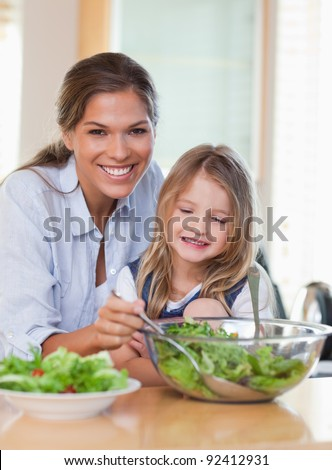 Portrait of a young mother and her daughter preparing a salad in their kitchen