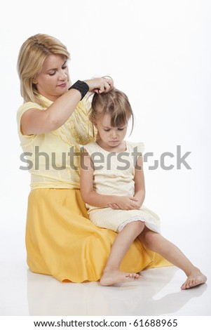 Portrait of a young mother trying to comfort her sad little daughter. Studio image.