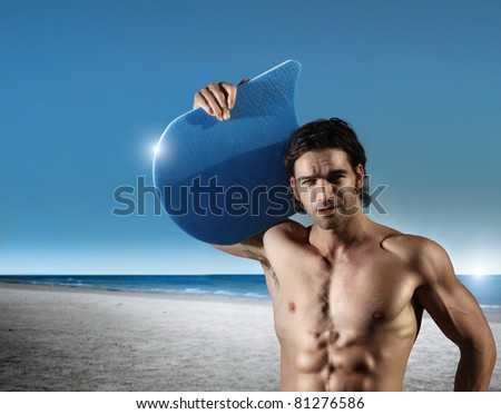 portrait of a young muscular male on the beach with blue sky and ocean in background