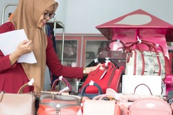 portrait of a young muslim  businesswoman smile holding paper checking her stock at fashion boutique, purse store and fabric display young entrepeneur concept -image