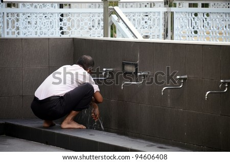Portrait of a young Muslim man perform ablution (wudhu)  before prayer
