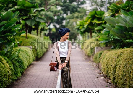 Portrait of a young Muslim woman in a hijab leaning on a railing in the park. She is wearing a blue turban and is elegantly dressed; she is of Arab, Malay, Asian descent and is attractive.