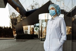 Portrait of a young nurse in a white coat, gloves and mask stands near the clinic and looking away. Stop coronavirus . Covid-19 Pandemic of the world