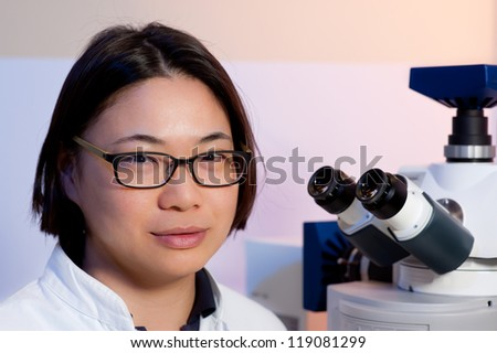 Portrait of a young oriental scientist in a microscopic room