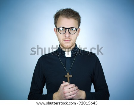 Portrait of a young pastor wearing a black shirt and clerical collar with a rosary and cross around his neck as he clasps his hands in prayer.