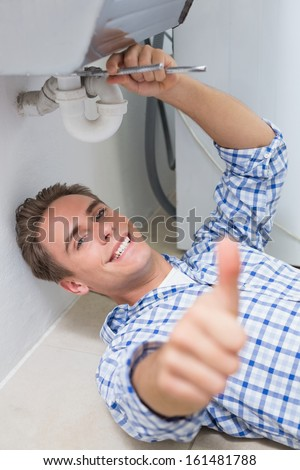 Portrait of a young plumber repairing washbasin drain while gesturing thumbs up in bathroom