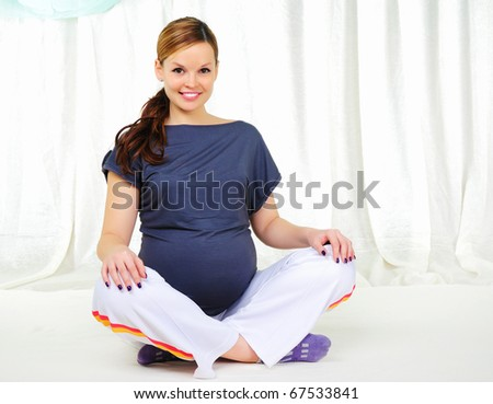Portrait of a young pregnant girl on a light background doing exercises
