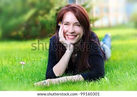 portrait of a young pretty smiling woman lying on green grass in the meadow  in summer