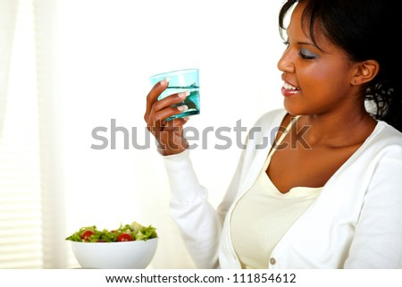 Portrait of a young pretty woman looking to a fresh water glass while smiling on a light background