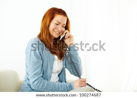 Portrait of a young pretty woman using a phone and smiling
