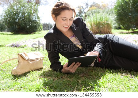 Portrait of a young professional woman laying down on green grass in a city park, using her digital tablet pad with touch screen, smiling.
