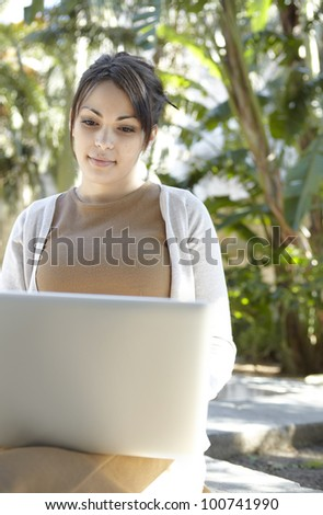 Portrait of a young professional woman using a laptop computer while sitting down in a park with golden sun light.