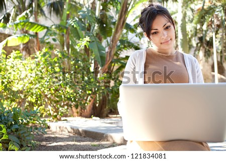 Portrait of a young professional woman using a laptop computer while sitting on a bench in a park, on a sunny day.