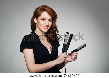 portrait of a young red hair woman, holding a comb and flat iron
