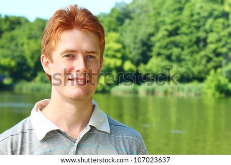 Portrait of a young red haired man over rural landscape