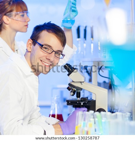Portrait of a young researcher microscoping in the life science (forensics, microbiology, biochemistry, genetics, oncology..)laboratory. Assistant scientist examining blue liquid solution in the back.