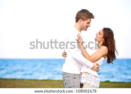 Portrait of a young romantic couple on a beach looking affectionately at each other