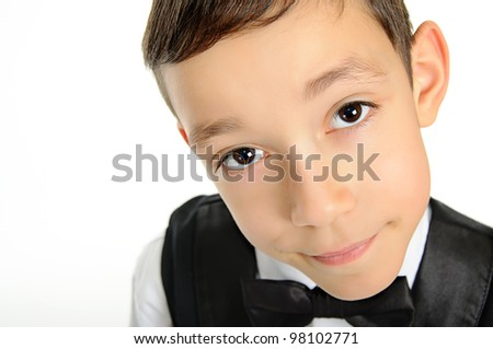 portrait of a young school boy in black suit with deep brown eyes looking at camera isolated on white background