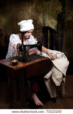 Portrait of a young seamstress with old sewing machine