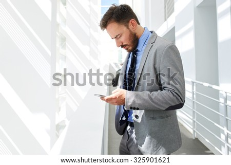 Portrait of a young serious businessman reading text message on his cell telephone while standing in big white corridor, confident male office worker chatting on mobile phone before business meeting