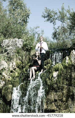 Portrait of a young sexy couple drinking a tea on waterfall - stock photo