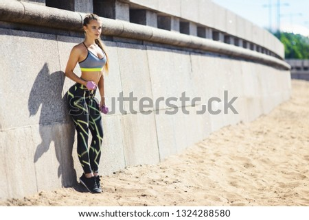 Portrait Of Young Fitness Woman Working Out With Dumbbells