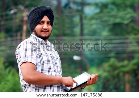 portrait of a young Sikh with tablet in India
