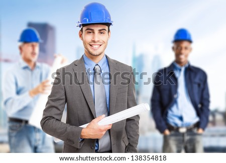 Portrait of a young smiling architect in front of his team