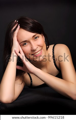 portrait of a young smiling brunette  woman with arms crossed under her hair on dark black background