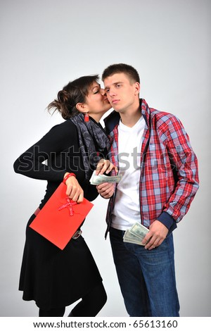 Portrait of a young smiling couple with shopping  bag and money