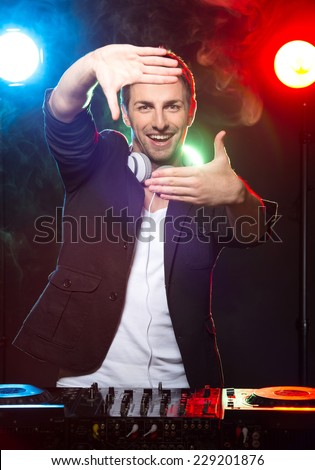 Portrait of a young smiling dj with mixer, on foggy background.