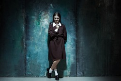 Portrait of a young smiling girl in school uniform as killer woman