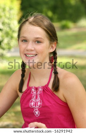 Portrait of a young smiling girl with braces in a park, outdoor setting