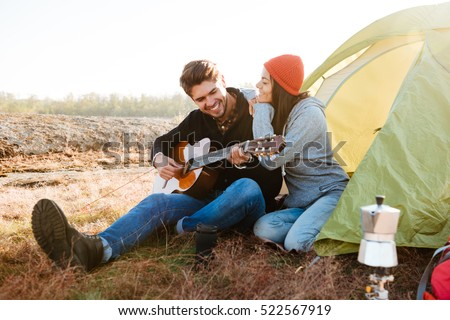 Portrait of a young smiling man playing guitar for his girlfriend sitting at the camping tent