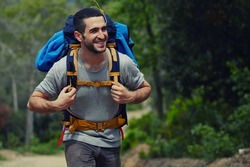 Portrait of a young smiling wanderer man with backpack goes on up the road with copy space, happy hiker walking lonely in mountains at summer day, traveler enjoying his recreation time in nature