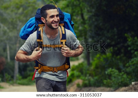 Shutterstock Portrait of a young smiling wanderer man with backpack goes on up the road with copy space, happy hiker walking lonely in mountains at summer day, traveler enjoying his recreation time in nature