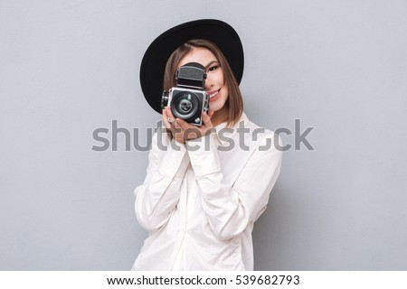 Portrait of a young smiling woman filming with retro camera isolated on the gray background #539682793