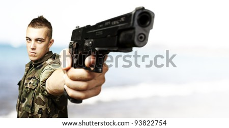 portrait of a young soldier aiming with a gun against a beach background