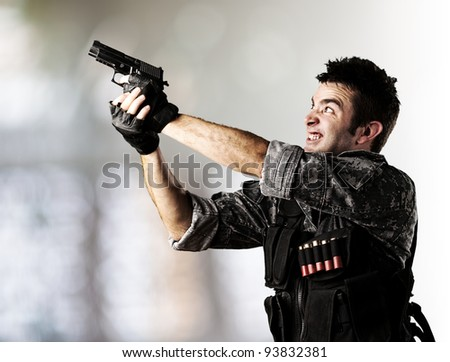 portrait of a young soldier aiming with a gun indoor